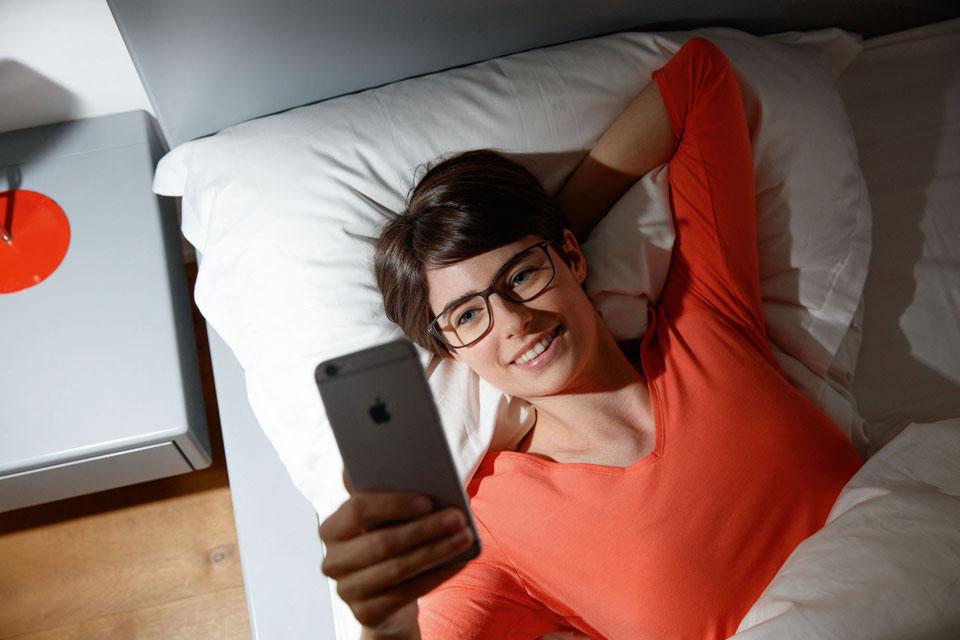Frau mit iPhone im Bett